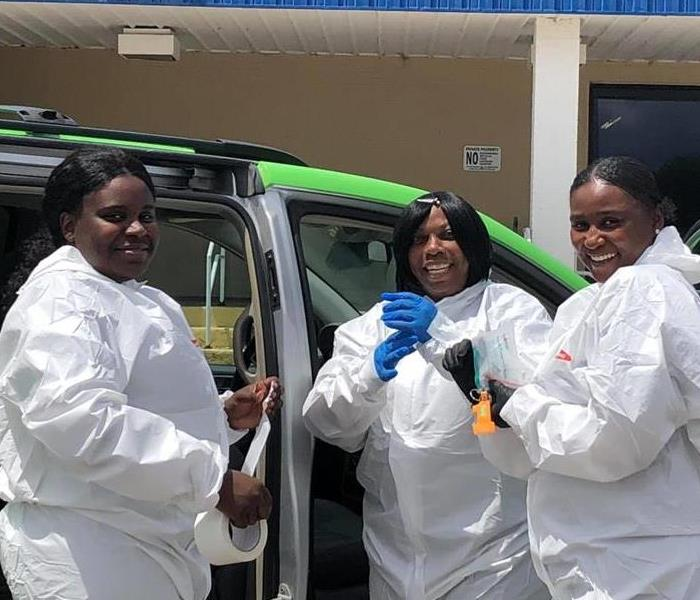 three women dressed in PPE suits