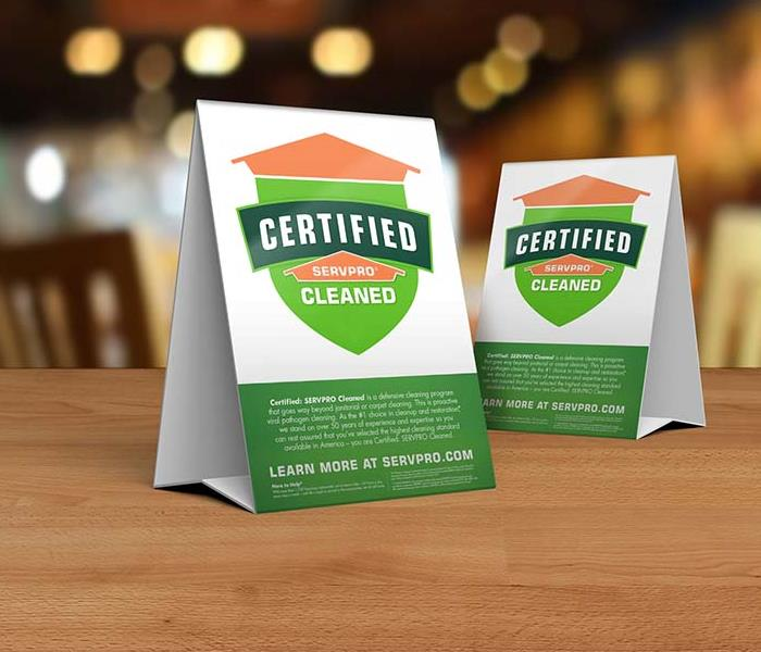 table tent signs describing the Certified: SERVPRO Cleaned program on top of wooden table top